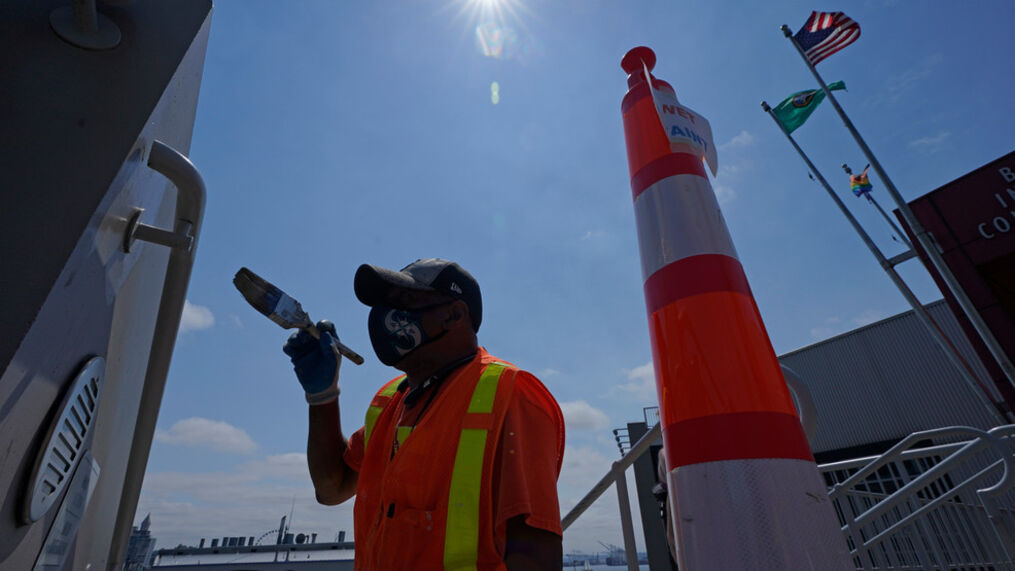 FILE - John Ford paints near a railing at the Bell Street Cruise Terminal at Pier 66, Wednesday, June 30, 2021, saying it was only taking about 10 minutes for his paint to be dry enough to touch. (AP Photo/Ted S. Warren)