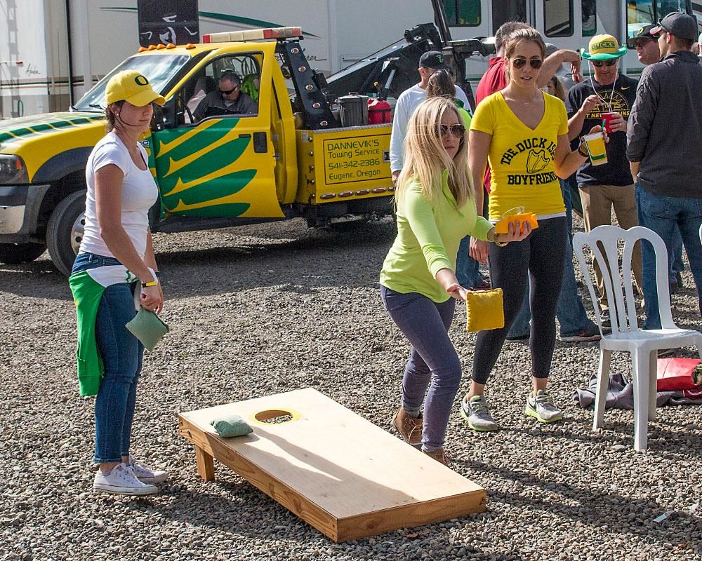 Chelsea Miller and Maddy Walton take a turn at a game of corn hole while tailgating on Saturday afternoon in the parking lot of Autzen Stadium. Katie Pietzold, Oregon News Lab