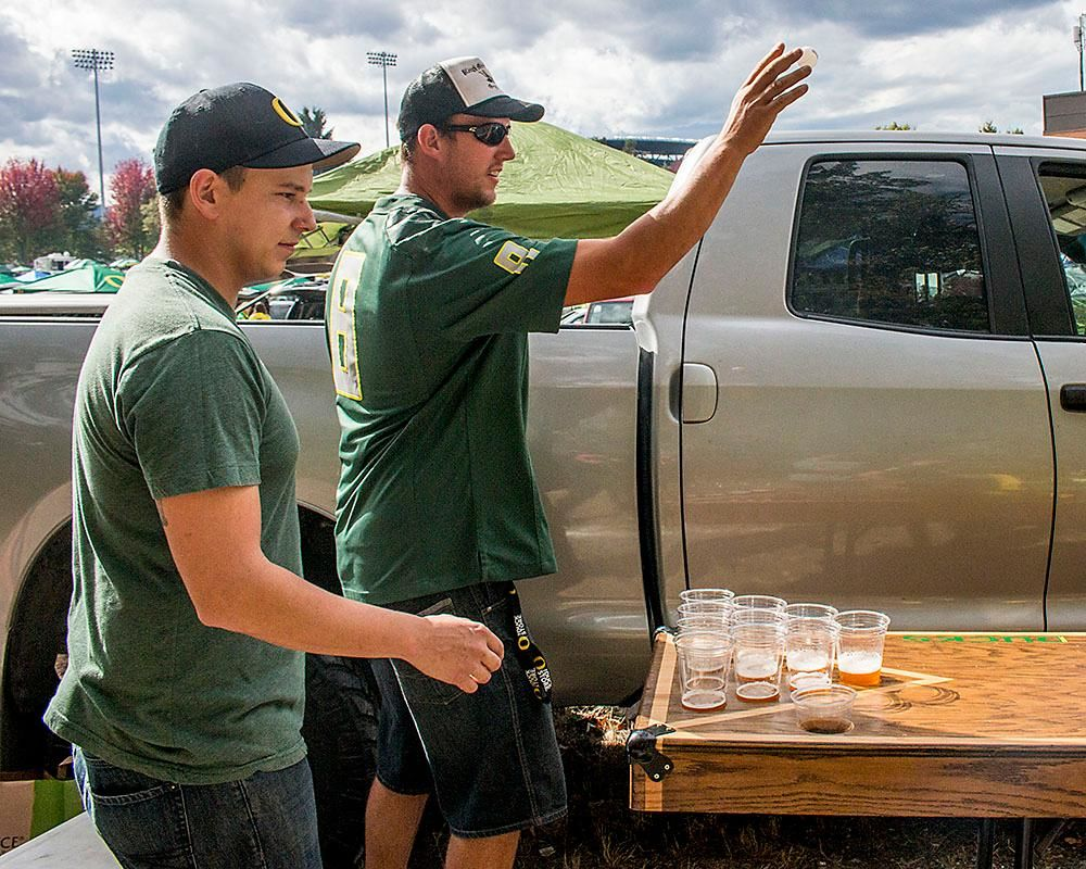 Jake Krumdeack and Bobby De La Cruz play a round of beer pong with their friends during a tailgate on Saturday afternoon across from Autzen Stadium. Katie Pietzold, Oregon News Lab