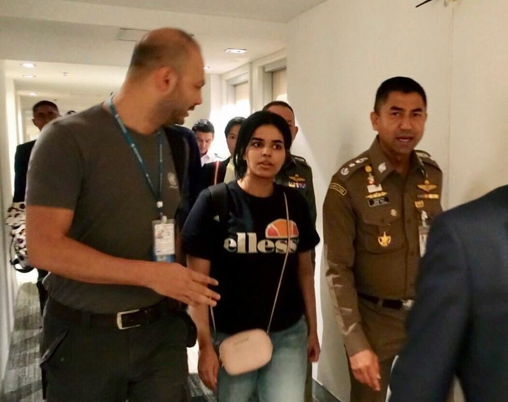 In this photo released by the Immigration Police, Chief of Immigration Police Maj. Gen. Surachate Hakparn, right, walks with Saudi woman Rahaf Mohammed Alqunun before leaving the Suvarnabhumi Airport in Bangkok Monday, Jan. 7, 2019. A Saudi woman who says she is fleeing abuse by her family and wants asylum in Australia has sent out desperate pleas for help over social media. Rahaf Mohammed Alqunun, 18, began posting on Twitter late Saturday after her passport was taken away when she arrived on a flight from Kuwait. (Immigration police via AP)