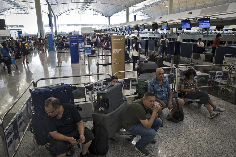 Travelers wait at the check-in counters in the departure hall of the Hong Kong International Airport in Hong Kong, Tuesday, Aug. 13, 2019.{&nbsp;} (AP Photo/Vincent Thian)<p></p>