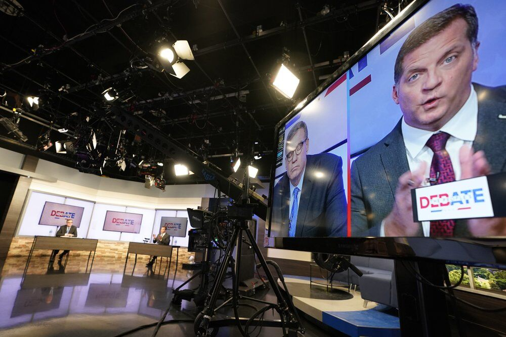 <p>U.S. Sen. Mark Warner, D-Va., left, and Republican challenger Daniel Gade, right, are displayed on a television monitor during a debate at a television studio Tuesday Oct. 13, 2020, in Richmond, Va. (AP Photo/Steve Helber)</p>
