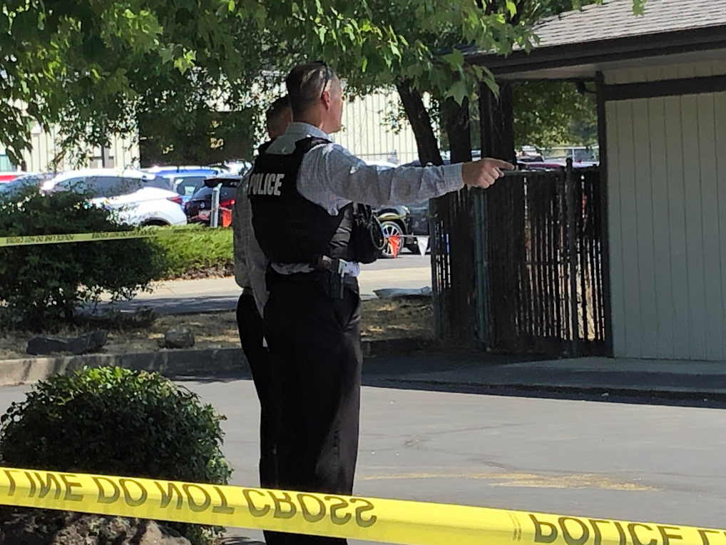 Pictured is a police officer in a bullet-proof vest, pointing and talking to another person. (Carsyn Currier/News 10)