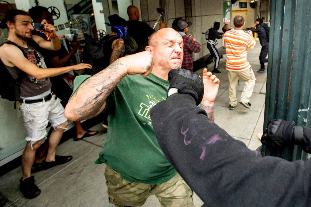 "A man tussles with protesters against right-wing demonstrators following an ""End Domestic Terrorism"" rally in Portland, Ore., on Saturday, Aug. 17, 2019. Although the main protest remained largely peaceful, some skirmishes erupted in the following hours and police detained multiple protesters. (AP Photo/Noah Berger)"