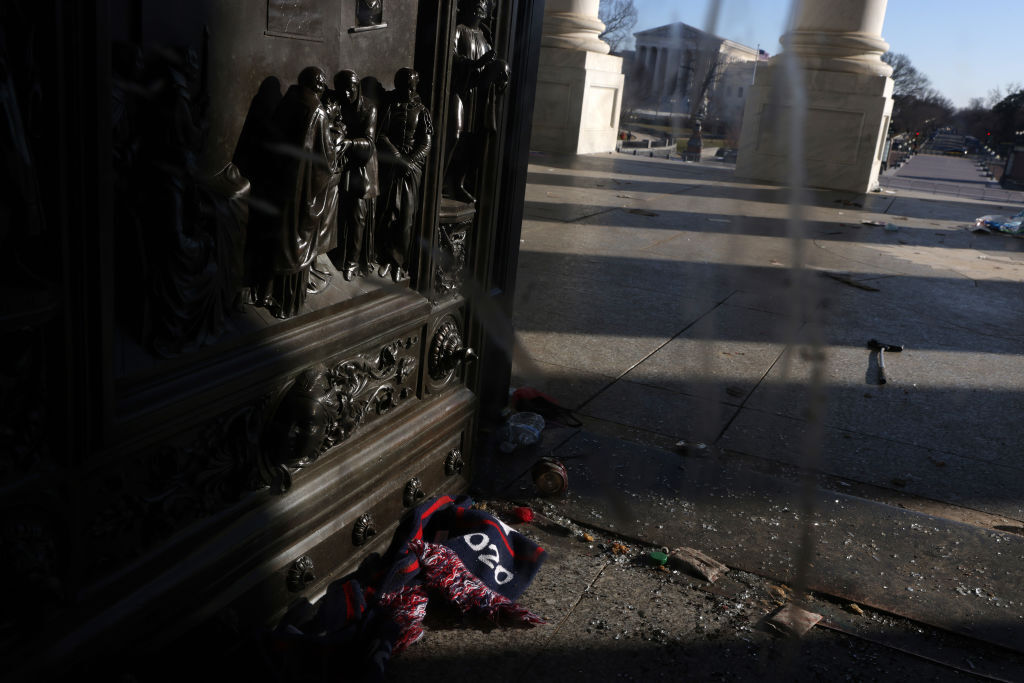 WASHINGTON, DC - JANUARY 07:  A scarf is left behind outside a damaged entrance of the U.S. Capitol January 7, 2021 in Washington, DC. The U.S. Congress has finished the certification for President-elect Joe Biden and Vice President-elect Kamala Harris' electoral college win after pro-Trump mobs stormed the Capitol and temporarily stopped the process. (Photo by Alex Wong/Getty Images)
