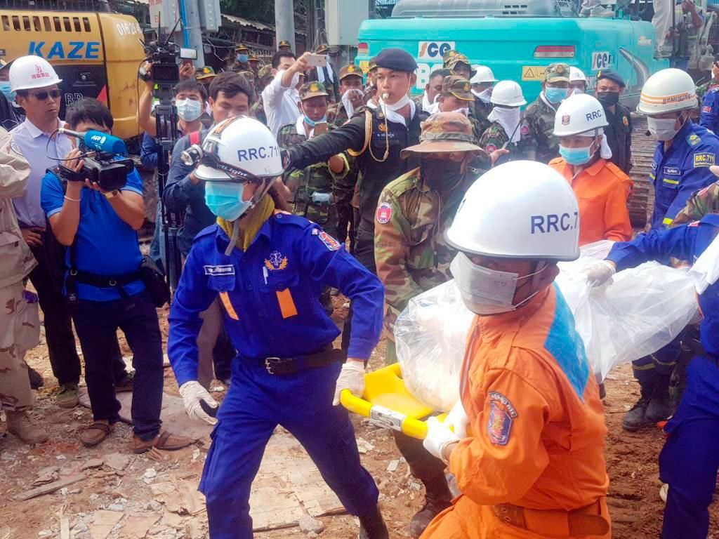 In this photo provided by Preah Sihanouk Provincial Authority, rescuers carry the body of a victim at the site of a building collapse, Monday, June 24, 2019, in Preah Sihanouk province, Cambodia.{ } (Preah Sihanouk Provincial Authority via AP)