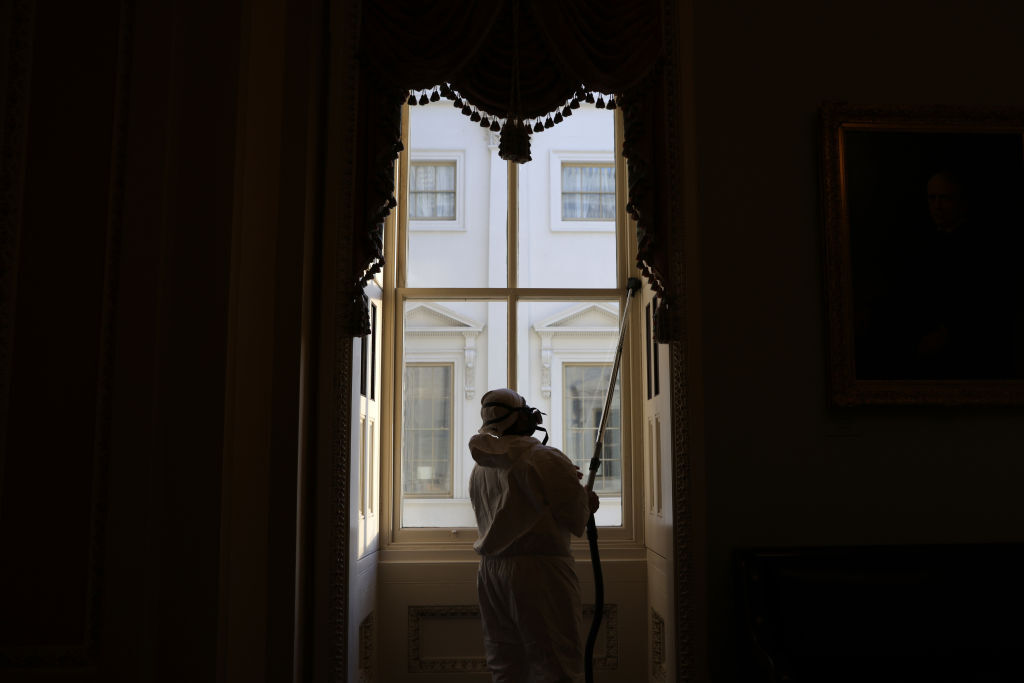 WASHINGTON, DC - JANUARY 07:  A member of a cleaning crew vacuums a window at the U.S. Capitol January 7, 2021 in Washington, DC. The U.S. Congress has finished the certification for President-elect Joe Biden and Vice President-elect Kamala Harris' electoral college win after pro-Trump mobs stormed the Capitol and temporarily stopped the process. (Photo by Alex Wong/Getty Images)