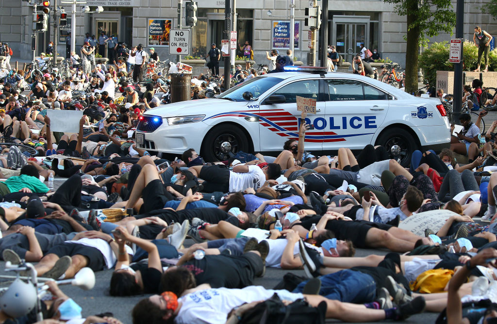 WASHINGTON, DC - JUNE 03: Demonstrators lay down near a police vehicle during a peaceful protest against police brutality and the death of George Floyd, on June 3, 2020 in Washington, DC. Protests in cities throughout the country have been held after the death of George Floyd, a black man who was killed in police custody in Minneapolis on May 25.  (Photo by Tasos Katopodis/Getty Images)