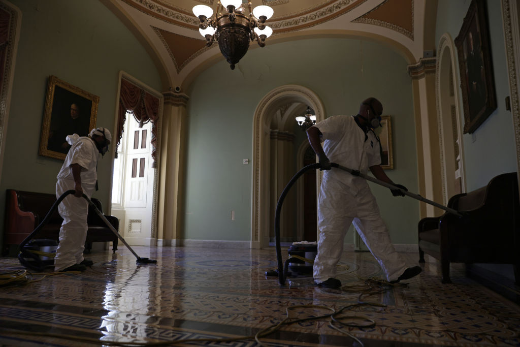 WASHINGTON, DC - JANUARY 07:  A cleaning crew vacuums the floor of a hallway at the U.S. Capitol January 7, 2021 in Washington, DC. The U.S. Congress has finished the certification for President-elect Joe Biden and Vice President-elect Kamala Harris' electoral college win after pro-Trump mobs stormed the Capitol and temporarily stopped the process. (Photo by Alex Wong/Getty Images)