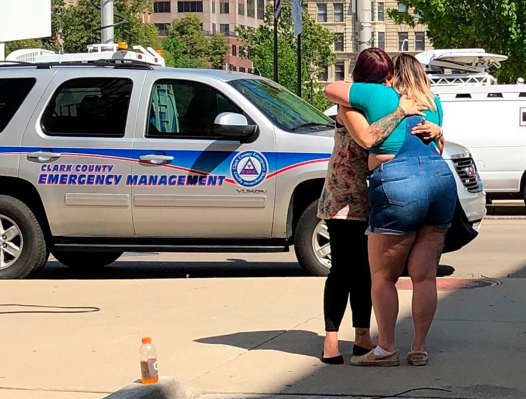 Residents comfort each other as they await word on whether they know any of the victims of a mass shooting on Sunday, Aug. 4, 2019, in Dayton, Ohio. (AP Photo/Julie Carr Smyth)