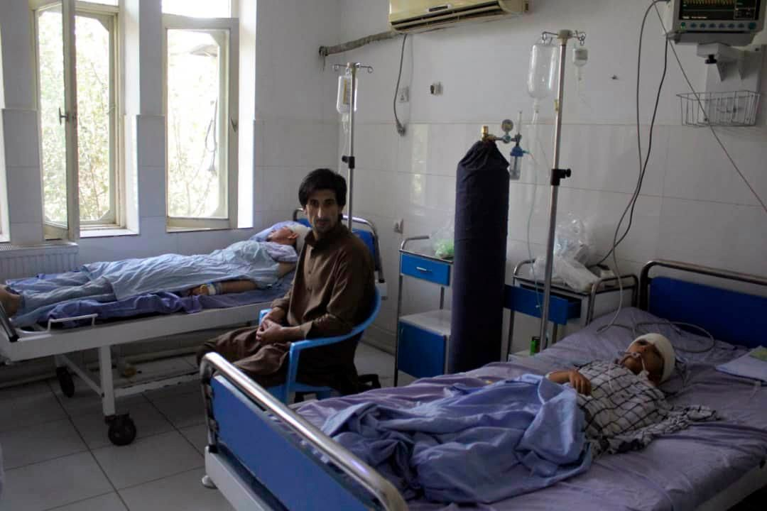 A wounded man and a young boy receive treatment in a hospital, after a fight between Taliban and Afghan security forces in Kunduz province on Saturday, north of Kabul, Afghanistan, Sunday, Sept. 1, 2019.{ } (AP Photo/Bashir Khan Safi)