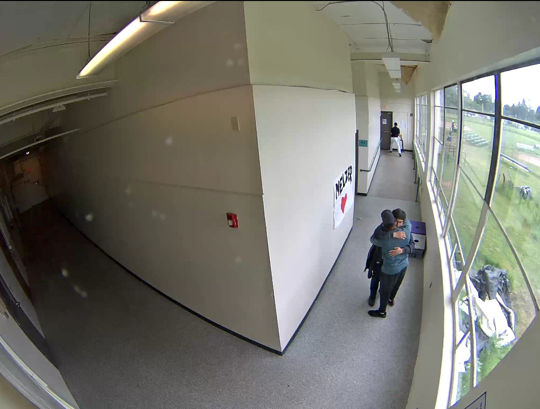 Parkrose High School security guard and football coach Keanon Lowe can be seen embracing student Angel Granados-Diaz last may in this security footage released by the Multnomah County District Attorney's Office on Friday. At the far end of the hall, a staff member can be seen taking the gun from the scene.