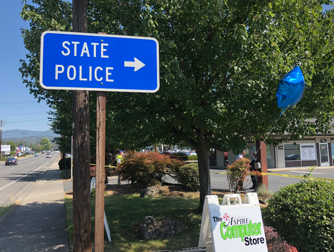Pictured is a sign pointing toward Oregon State Police offices in Grants Pass. In the background is caution tape marking the area off from the public. (Carsyn Currier/New 10)