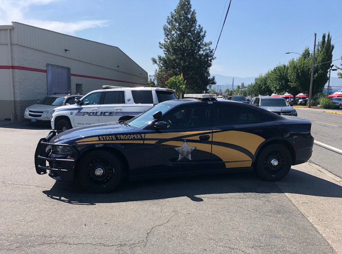 Pictured is an Oregon State Police squad car with a Grants Pass Police SUV parked in the background (Carsyn Currier/News 10)