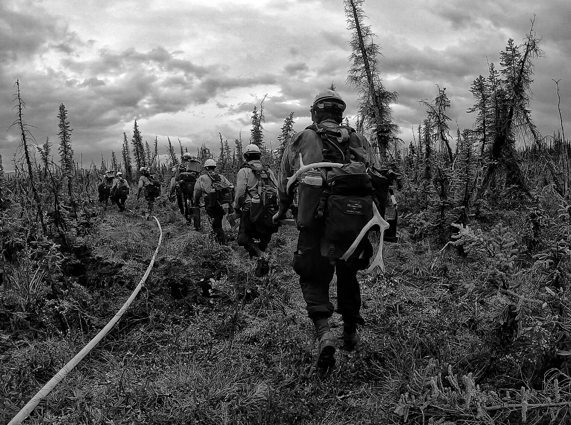 A black and white photo of firefighters walking in a line through the Alaskan wilderness. The firefighter last in line has a pair of antlers hooked onto his backpack. (Courtesy Medford Crew 10){ }
