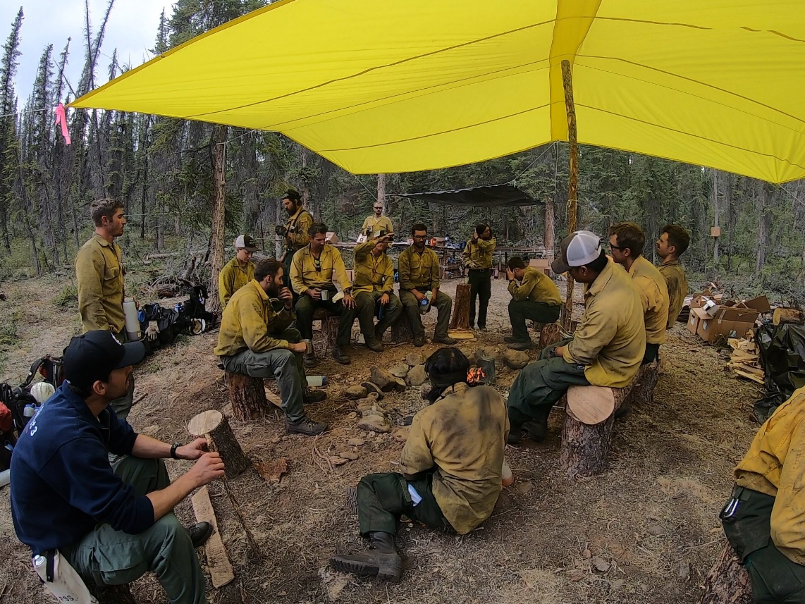 The crew at fire camp, seen sitting on tree stumps used as chairs. (Courtesy Medford Crew 10)