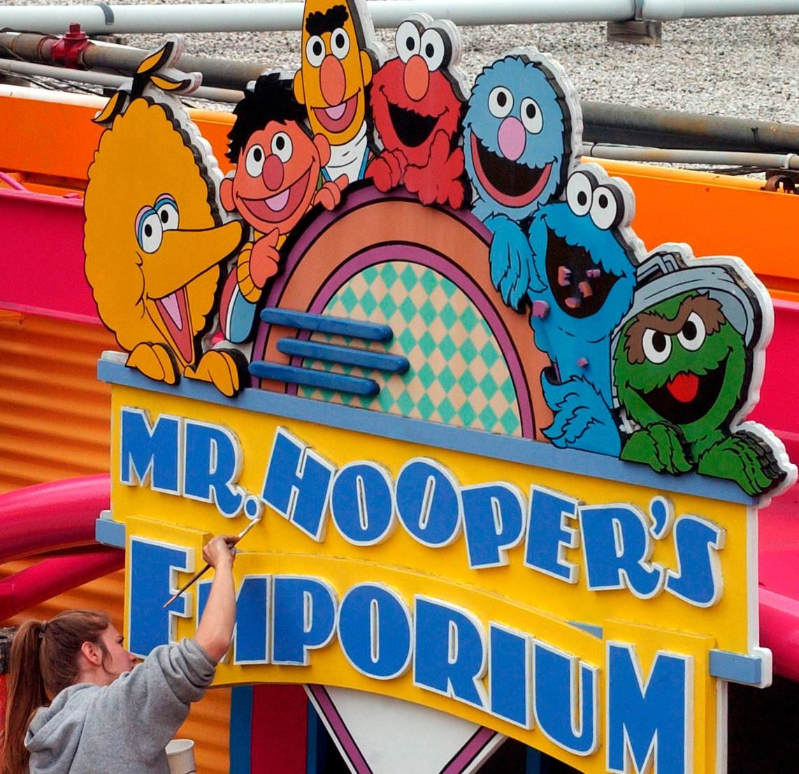 FILE - In this May 4, 2005, file photo, Tessa Meier puts some new paint on the sign outside Mr. Hooper's Emporium to get ready for opening day at Sesame Place in Langhorne, Pa. (Harry Sircely/Bucks County Courier Times via AP, File)