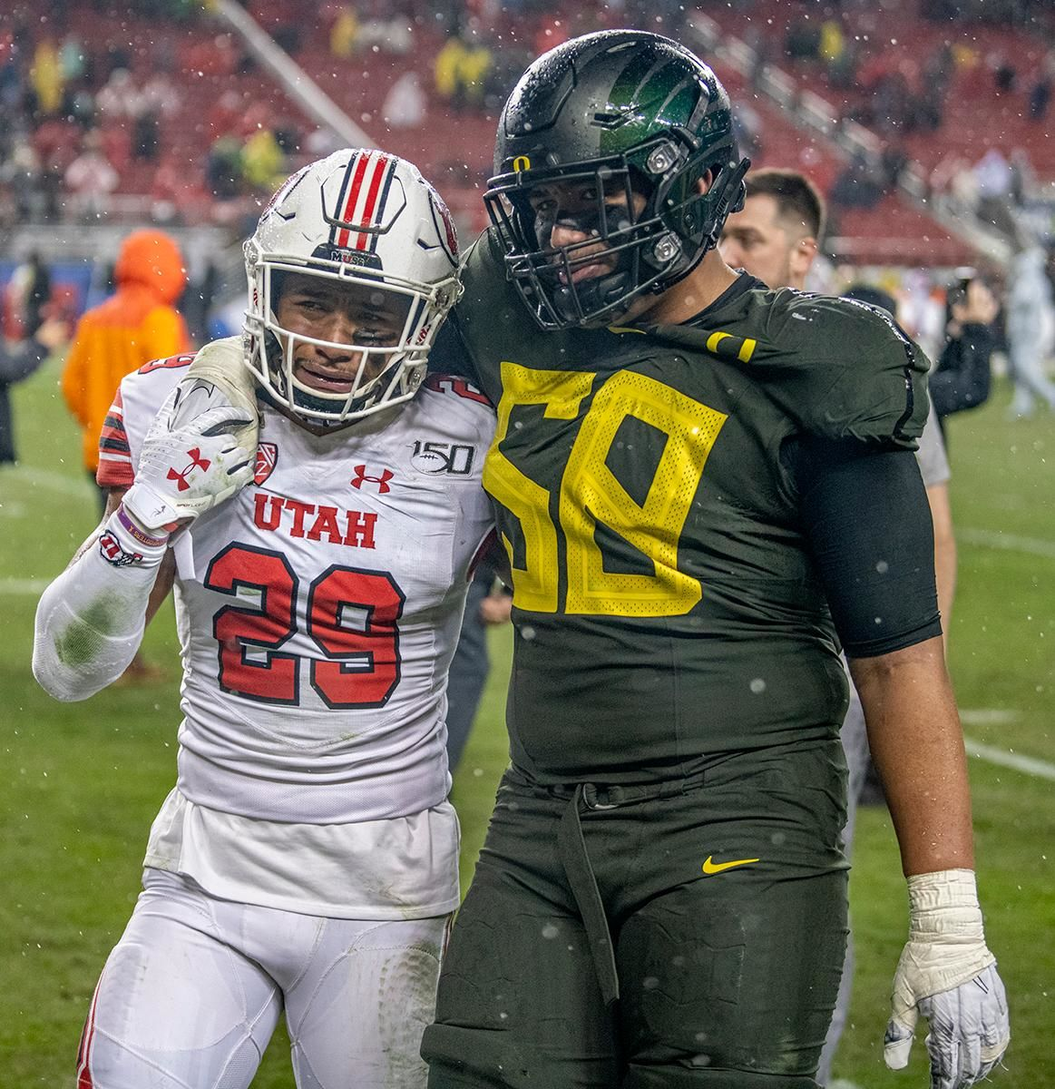 Utah's defensive back Nephi Sewell, #29, and brother Oregon's left tackle Penei Sewell, #58, share a moment of emotion on their way to thier parents in the stand.  The University of Oregon Ducks defeated the University of Utah Utes 37-15 for the Pac 12 Championship Friday night at Levi's Stadium. Oregon's running back CJ Verdell, #7, rushed for 203 all-purpose yard along with three touchdowns for the night. Verdell was named the games M-V-P for his performace. Oregon's safey Brady Breeze, #25, contributed 9 tackles and one interception. Oregon's defensive end Kayvon Thibodeaux, #5, sacked Utah's quarterback Tyler Huntly, #1, for a total of three times. Oregon's quarterback Justin Herbert, #10, passed for 193 yards with one touchdown. The Oregon Ducks will represent the Pac 12 for the upcoming Rose Bowl game in the new year. Photo by Jeffrey Price
