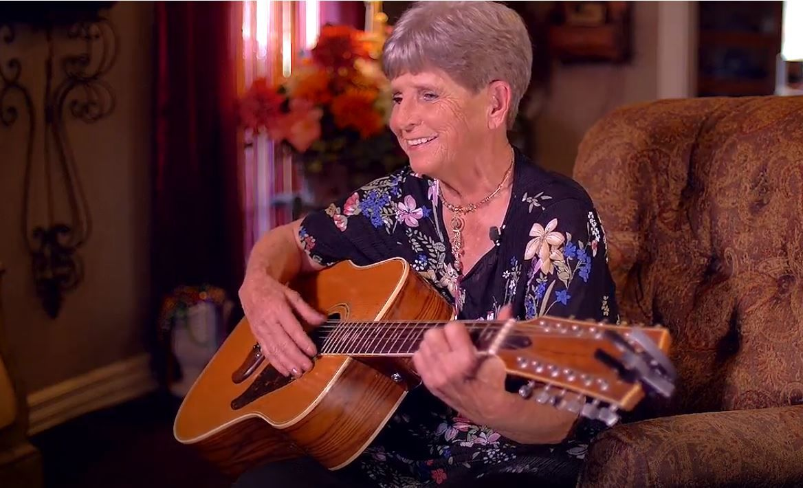 Shirley Crecelius plays her guitar and sings about her husband. (KTUL photo)