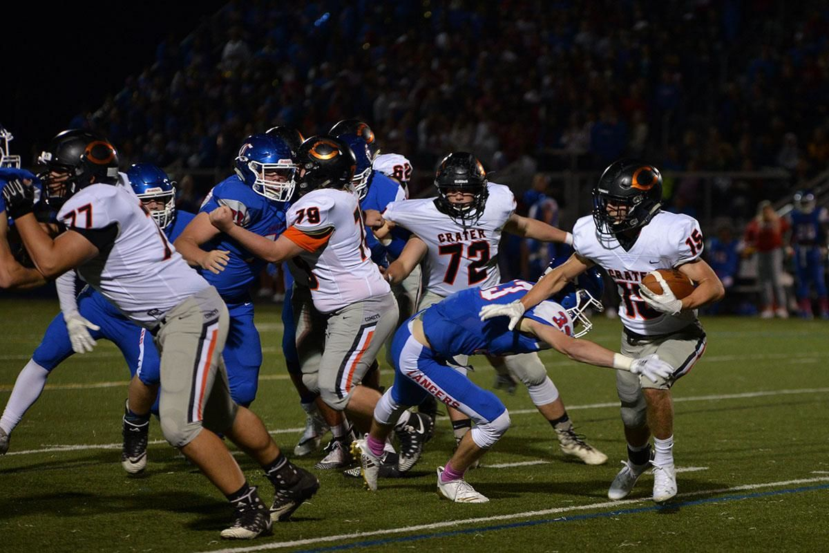 Crater running back Gavin Acrey (15) stiff arms Churchill linebacker Mitchell Whittier. The Churchill Lancers dominated the Crater Comets 58-20 in front of a packed Homecoming crowd. With the win Churchill advances to the 5A district playoffs. Photo by Emilee Jackson