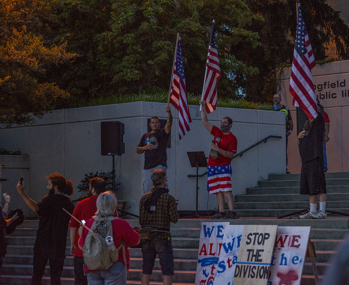 "Flags are held high as ""Star-spangled banner"" is played to close out the rally.  About 250 people gathered at the Springfield, Oregon, library for what was billed as an All Lives Matter rally Friday at 7 p.m. About a dozen counter protesters also attended. The event was mostly peaceful, although a couple of minor scuffles broke out and one man was taken into custody by the Springfield police. By 9:30 p.m. both the protesters and the counter protesters dispersed. Photo by Jeremy Williams"