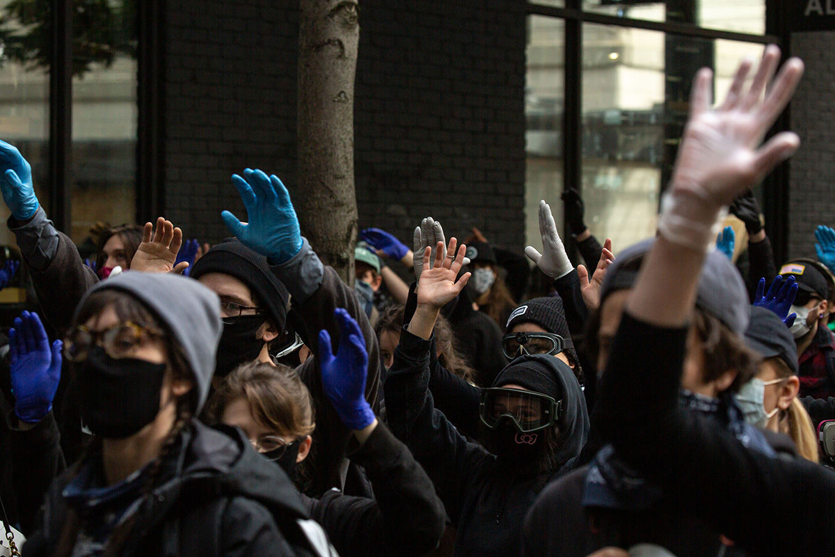 SEATTLE, WA - MAY 31: Demonstrators walk with their hands up to protest the recent death of George Floyd on May 31, 2020 in Seattle, Washington. Protests due to the recent death of George Floyd took place in Seattle and its suburb of Bellevue, with disturbances in Bellevue and at least one burnt automobile there.(Photo by David Ryder/Getty Images)