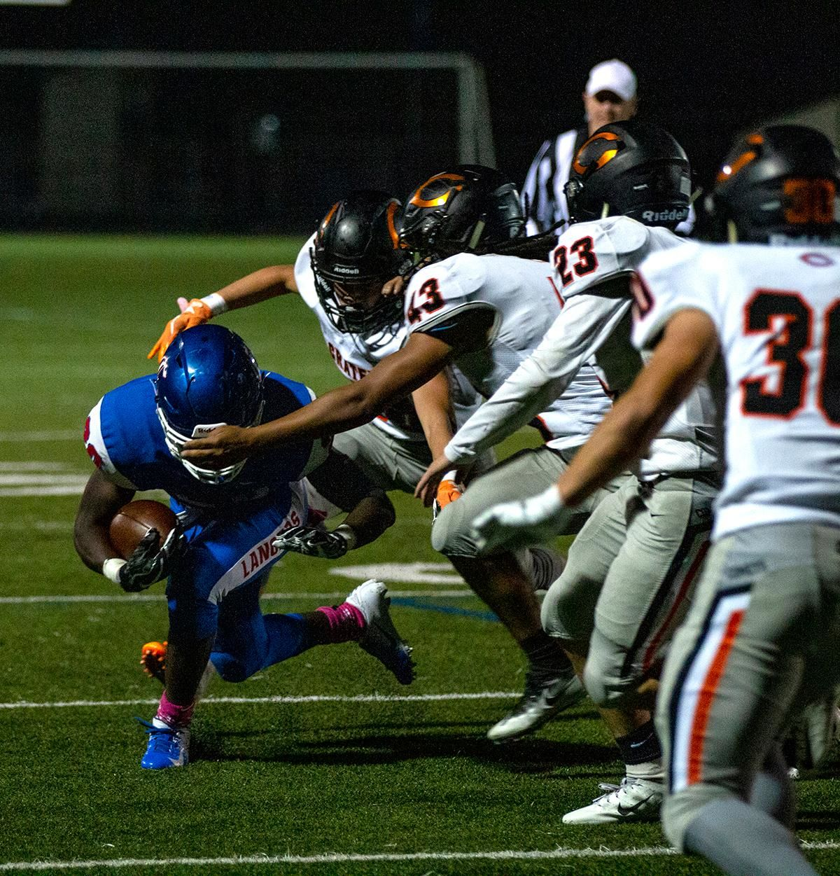 Churchill running back Deonte Jones (#20) ducking through the reach of Crater defenders. The Churchill Lancers dominated the Crater Comets 58 – 20 in front of a pact Homecoming crowd. With the win Churchill advances to the 5A district playoffs. Photo by Payton Bruni