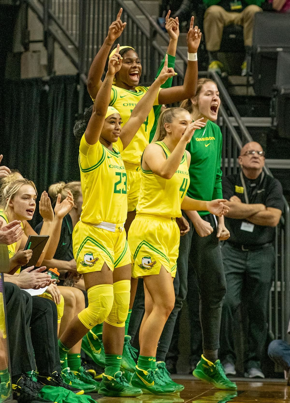 University of Oregon Ducks, left to right, Minyon Moore, #23, Jaz Shelley, #4, and Ruthy Hebard, #24, celebrate from the bench after a score. The University of Oregon Ducks women's basketball team defeated the Utah St. Aggies 109 – 52 in Matt Knight Arena Wednesday evening. Taylor Chavez led the Ducks with 25 points including six three-pointers. Jaz Shelley added 15 for the Ducks. Ruthy Hebard needed six rebounds to have an accumulated career 1000 rebounds; she pulled down 15 and scored 19 points for a double-double. Sabrina Ionescu needed four points to have an accumulated career 2000 points; she scored 16 points and had 12 assists for a double-double. Photo by Jeffrey Price