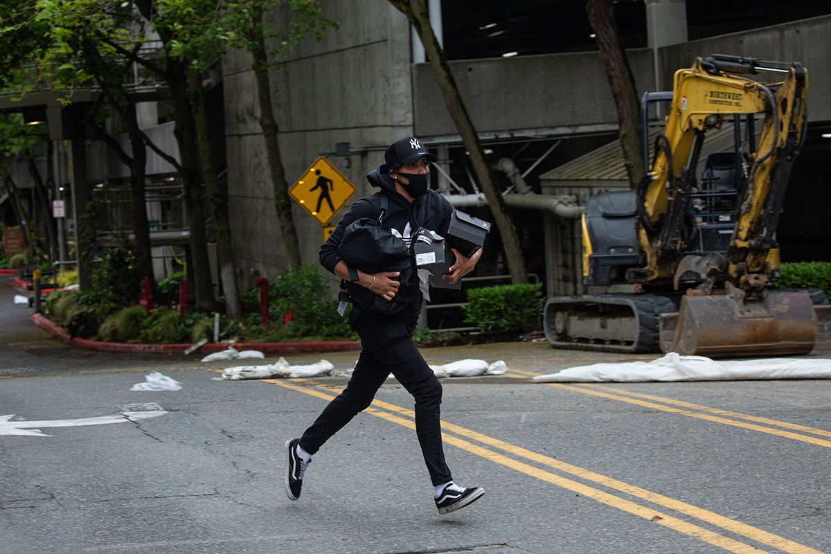 BELLEVUE, WA - MAY 31: A person runs from Bellevue Square Mall while carrying items on May 31, 2020 in Bellevue, Washington. Protests due to the recent death of George Floyd took place in Bellevue in addition to Seattle, with looting in Bellevue and at least one burned automobile there. (Photo by David Ryder/Getty Images)