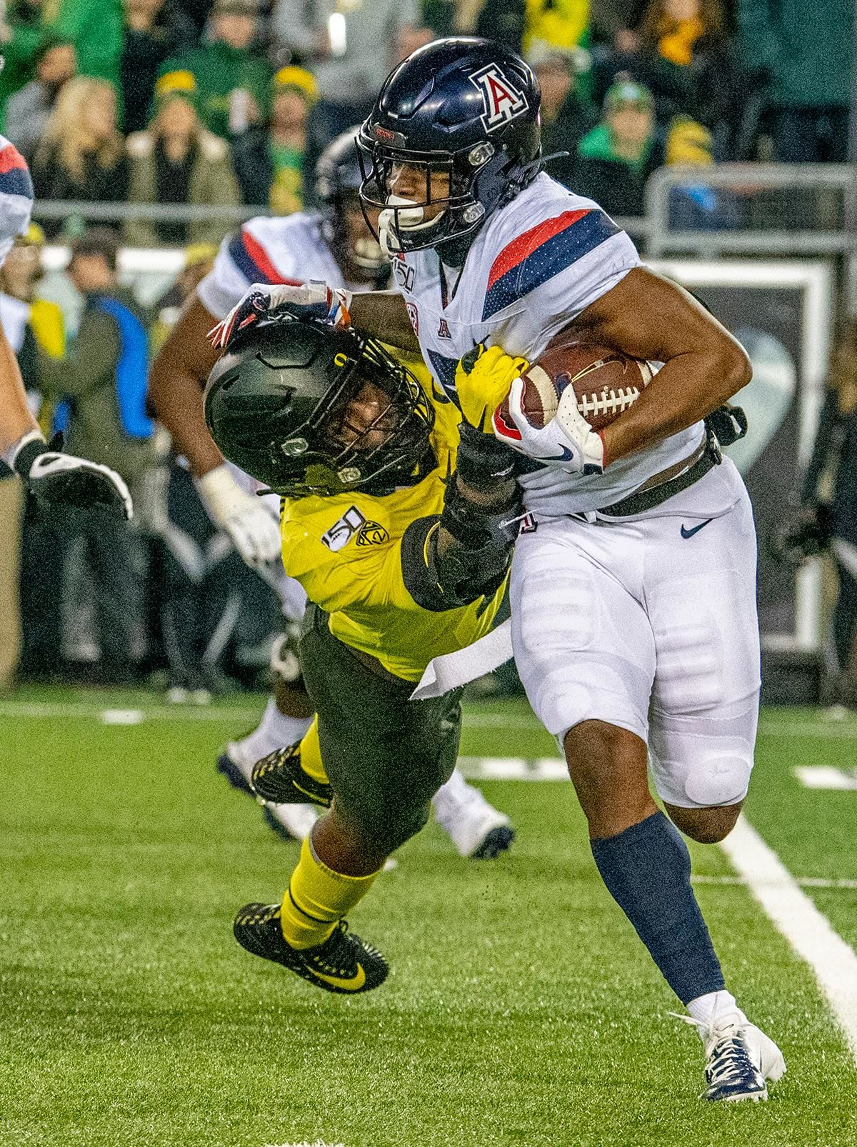 Oregon's defensive end Kayvon Thibodeaux, #5, reaches out and grabs Arizona's quaterback Khalil Tate, #14, for a sack and loss of yards. The University of Oregon Ducks beat the University of Arizona Wildcats 34 - 6 home at Autzen Stadium. Oregon's Quarterback Justin Herbert threw for 333 yards and four touchdowns. He surpasses 10,000 career passing yards in his senior year. Oregon's wide receiver Juwan Johnson caught 5 receptions for 93 yards along with one touchdown. The Oregon defense sacked Arizona's quarterback's for a total of six times. With the win, the Ducks clinch the PAC 12 North and will head to the PAC 12 Championship on December 6th 2019.  Photo by Jeffrey Price