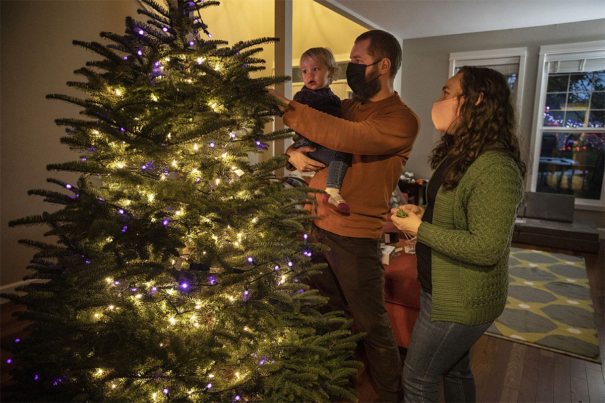Ani Sirois places lights and decorations on the family's Christmas tree with daughter Ida, 2, and husband, Chadwick, at their home on Tuesday, Nov. 24, 2020 in Portland, Ore. (AP Photo/Paula Bronstein)