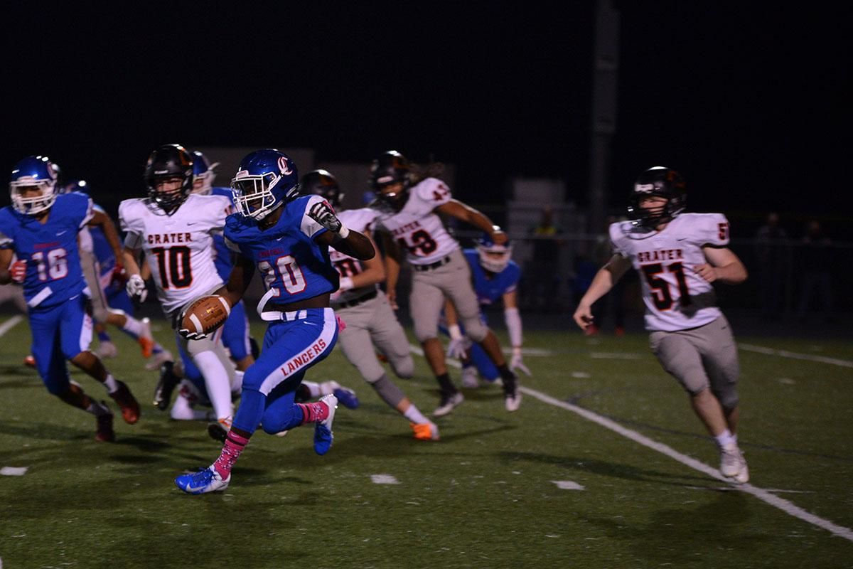 Churchill running back Deonte Jones (20) sprints to the left. The Churchill Lancers dominated the Crater Comets 58-20 in front of a packed Homecoming crowd. With the win Churchill advances to the 5A district playoffs. Photo by Emilee Jackson