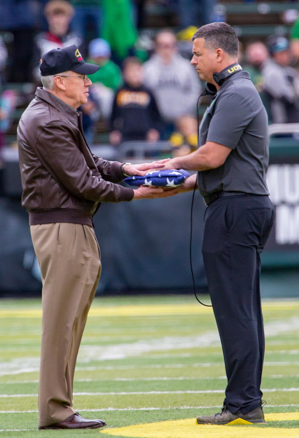 "Major General Raymond ""Fred"" Rees receives a flag from Oregon head coach Mario Cristobal during a flag ceremony at half time.  More than 35,000 fans turned out for the University of Oregon's annual spring football game. Mighty Oregon defeated the Fighting Ducks 20 to 13 during the Saturday afternoon game at Autzen Stadium in Eugene, Ore. on April 20, 2019. [Ben Lonergan for KVAL.com] - KVAL.com"