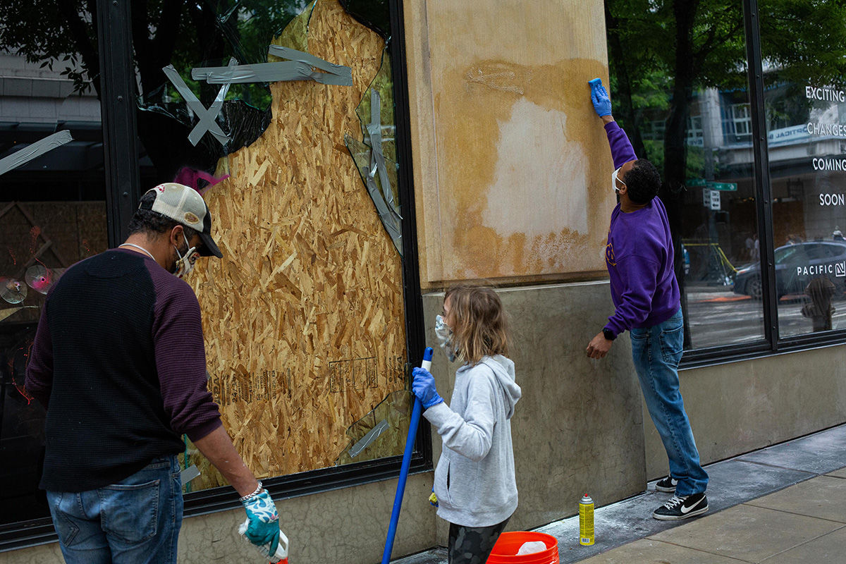 SEATTLE, WA - MAY 31: Volunteers help clean up a storefront on the day after violent protests due to the recent death of George Floyd on May 31, 2020 in Seattle, Washington. Protests began again peacefully Sunday after days of violent scenes in the city. (Photo by David Ryder/Getty Images)