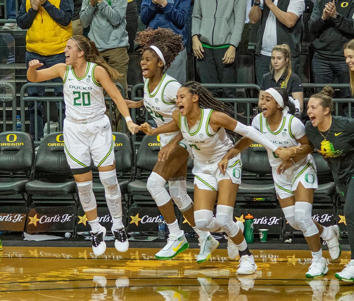 University of Oregon Ducks starters come off the bench to celebrate their teams victory over Stanford. From left to right: Sabrina Ionescu, #20; Ruthy Hebard, #24; Satou Sabally, #0, Minyon Moore, #23. The #6 University of Oregon Ducks women's basketball team defeated #3 Stanford Cardinal 87-55 in front of a sold out crowd of 12, 218 fans in Matthew Knight Arena. Sabrina Ionescu broke the all-time Oregon scoring record of 2,253 and ended the game with 37 points, 11 rebounds, another double-double. Satou Sabally added 18 points and 11 rebounds, also a double-double. Ruthy Hebard put up 11 points with 5 rebounds, and Minyon Moore added 10 points 3 rebounds. The Ducks next face off against Cal on Sunday, January 19, at 2 pm in Matthew Knight Arena. Photo by Dan Morrison