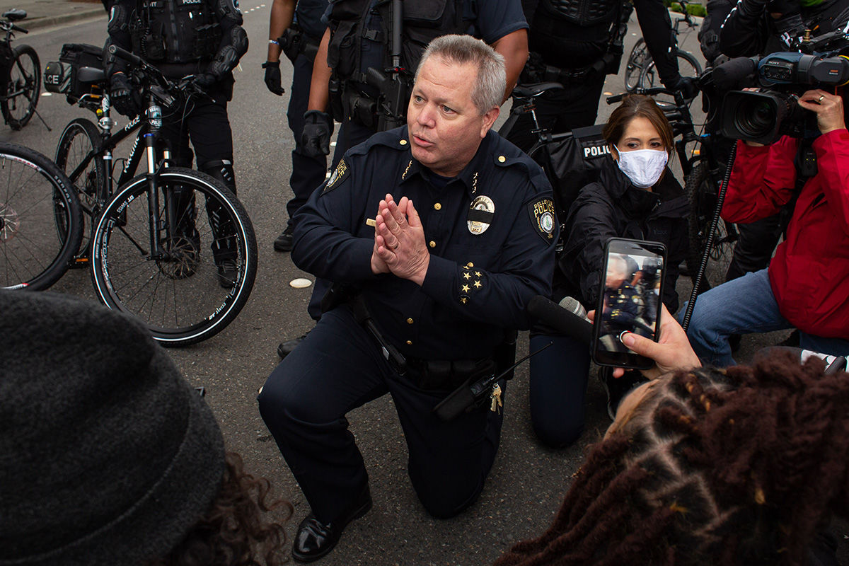 BELLEVUE, WA - MAY 31: Bellevue Police Chief Steve Mylett kneels next to demonstrators while talking with them during a gathering to protest the recent death of George Floyd on May 31, 2020 in Bellevue, Washington. Protests due to the recent death of George Floyd took place in Bellevue in addition to Seattle, with looting in Bellevue and at least one burned automobile there. (Photo by David Ryder/Getty Images)