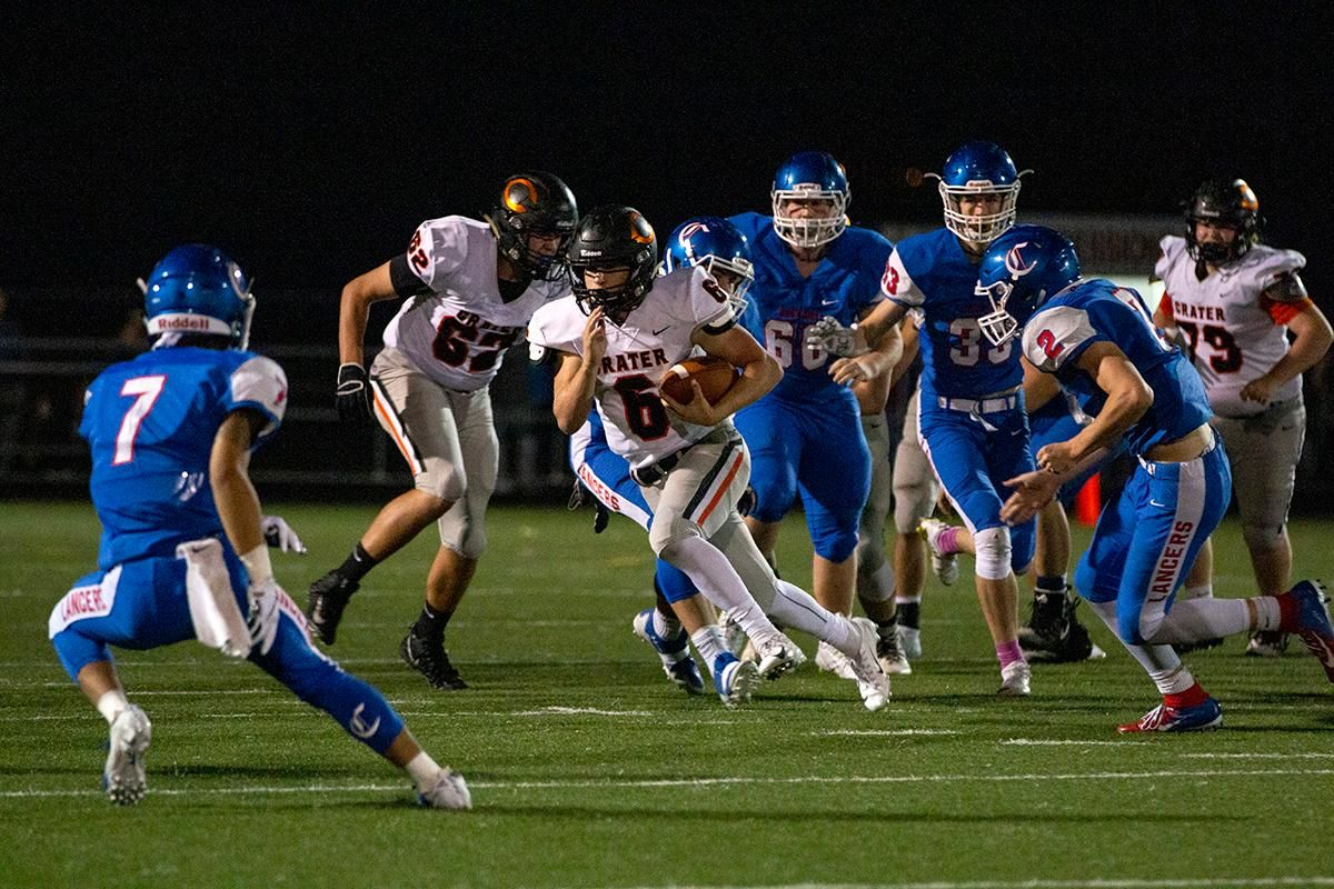 Crater quarterback Trever Davis (#6) runs from a pack of defenders. The Churchill Lancers dominated the Crater Comets 58 – 20 in front of a pact Homecoming crowd. With the win Churchill advances to the 5A district playoffs. Photo by Payton Bruni