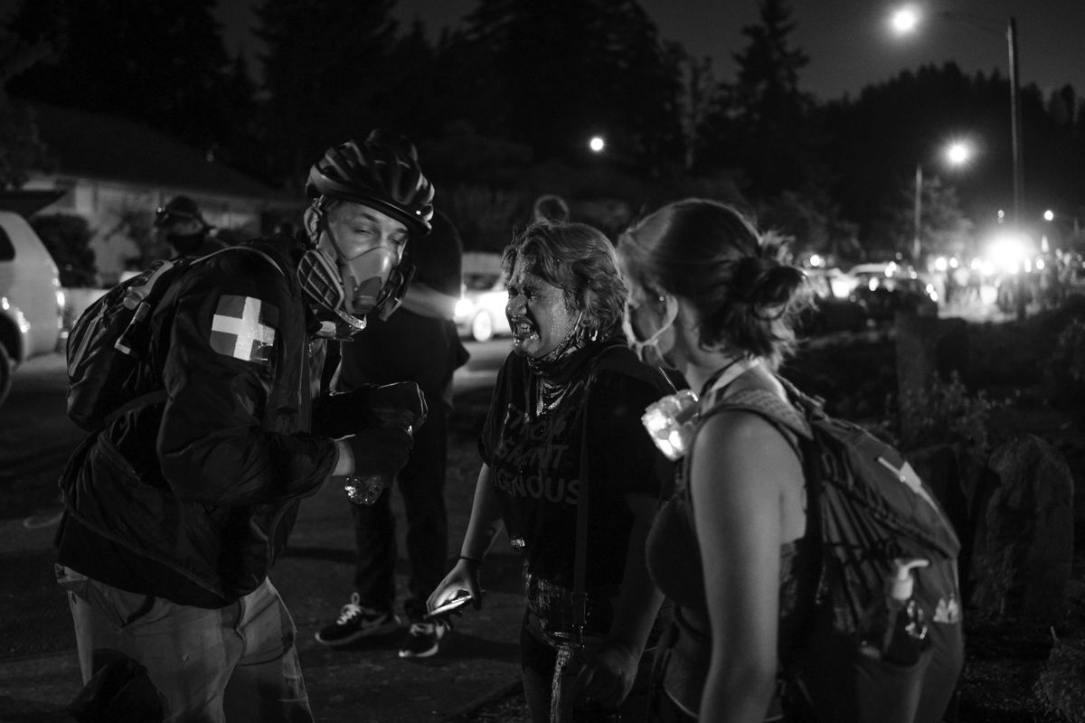 A Black Unity protester is treated by a medic after being sprayed in the face with wasp killer by an All Lives Matter counter protester. Approximately 150 Black Unity protesters marched through the Thurston neighborhood in Springfield Wednesday evening. At about 9 p.m. the protesters arrived at a Springfield police-manned roadblock. After about a 30-minute standoff, the protesters began to push against the barriers, which led to a physical confrontation and arrests. Photo by Robert Scherle