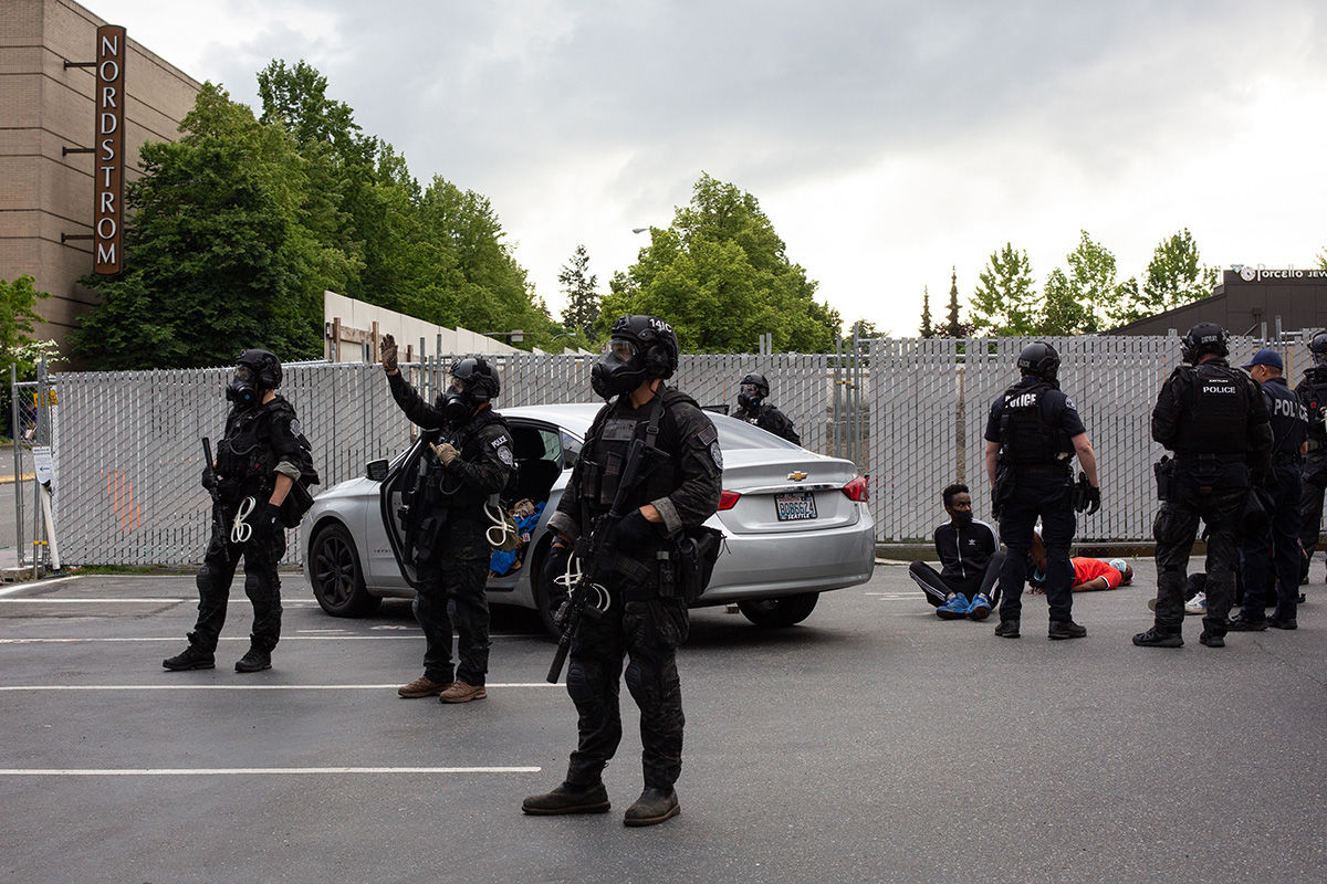 BELLEVUE, WA - MAY 31: Police detain a people near Bellevue Square Mall while another officer waves to people cursing at him after looting took place on May 31, 2020 in Bellevue, Washington. Protests due to the recent death of George Floyd took place in Bellevue in addition to Seattle, with looting in Bellevue and at least one burned automobile there. (Photo by David Ryder/Getty Images)