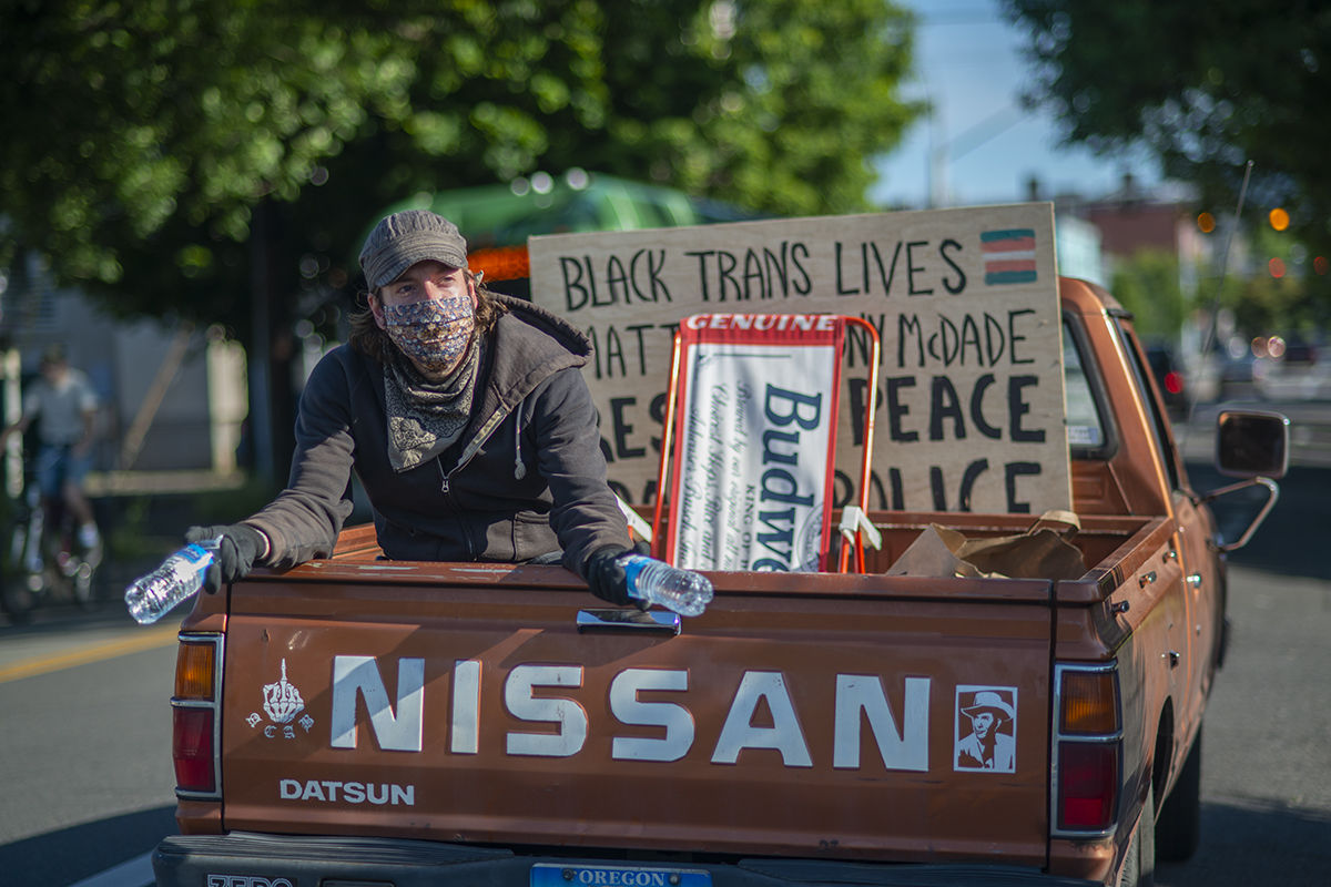A man hands out water to the protesters from the bed of his truck while following the path of the marching through downtown Eugene. Photo by Abby Libbert