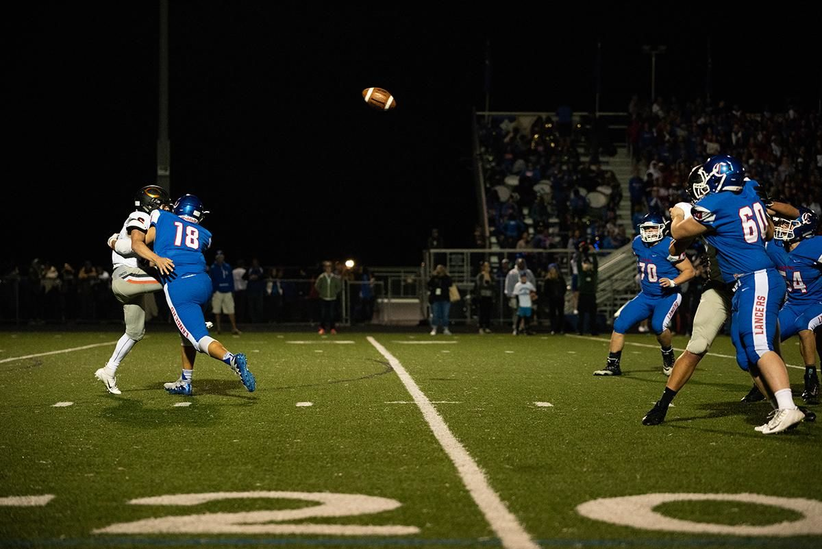 Churchill defender Dylan Carson drills the Crater quarterback to force an interception for a touchdown during friday nights homecoming game. The Churchill Lancers dominated the Crater Comets 58-20 in front of a packed Homecoming crowd.  With the win Churchill advances to the 5A district playoffs. Photo by Jeff Dean