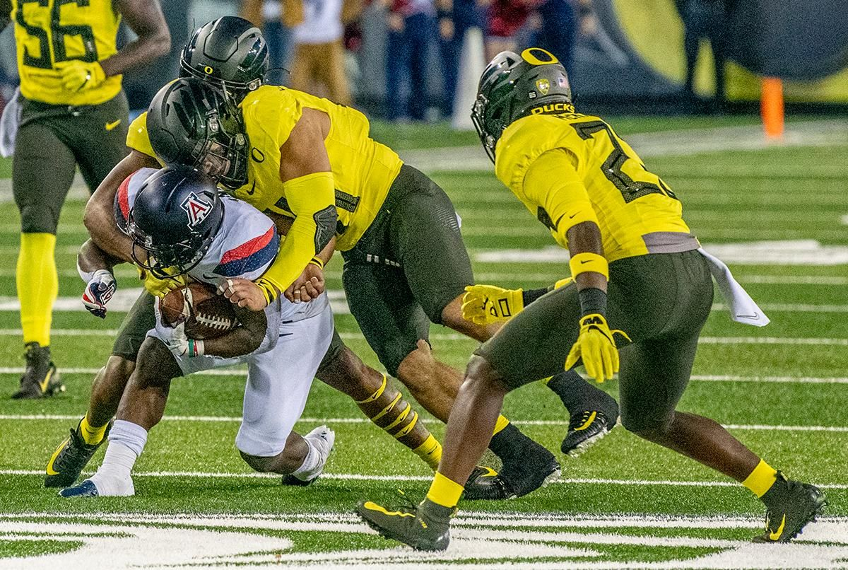 From left to right, Oregon's cornerback Deommodore Lenoir, #6, middle linebacker Issac Slade-Matautia, #41, and free safety Verone McKinley III, #23, bring down Arizona's running back J.J. Taylor, #21, after huge gain. The University of Oregon Ducks beat the University of Arizona Wildcats 34 - 6 home at Autzen Stadium. Oregon's Quarterback Justin Herbert threw for 333 yards and four touchdowns. He surpasses 10,000 career passing yards in his senior year. Oregon's wide receiver Juwan Johnson caught 5 receptions for 93 yards along with one touchdown. The Oregon defense sacked Arizona's quarterback's for a total of six times. With the win, the Ducks clinch the PAC 12 North and will head to the PAC 12 Championship on December 6th 2019.  Photo by Jeffrey Price