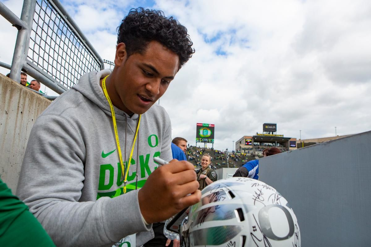 Former Oregon line backer Mase Funa signs the helmet of Oregon fan Tristan Dubois, 6. More than 35,000 fans turned out for the University of Oregon's annual spring football game. Mighty Oregon defeated the Fighting Ducks 20 to 13 during the Saturday afternoon game at Autzen Stadium in Eugene, Ore. on April 20, 2019. [Ben Lonergan for KVAL.com] - KVAL.comMase Funa