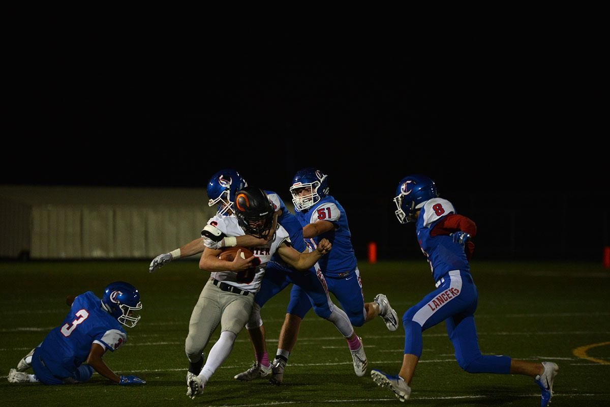 Crater quarterback Trever Davis (6) gets throttled by the Churchill defense. The Churchill Lancers dominated the Crater Comets 58-20 in front of a packed Homecoming crowd. With the win Churchill advances to the 5A district playoffs. Photo by Emilee Jackson