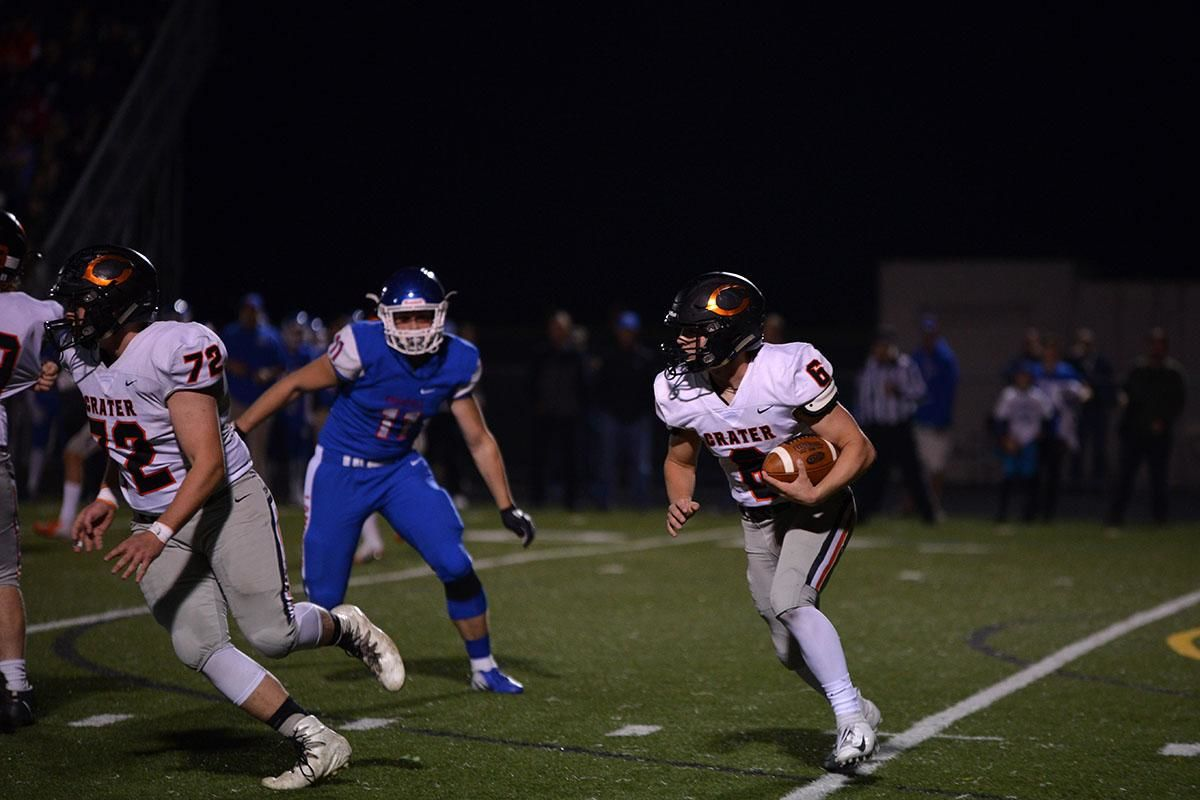 Crater quarter back Trever Davis (6) sprints left on a quarter back keeper. The Churchill Lancers dominated the Crater Comets 58-20 in front of a packed Homecoming crowd. With the win Churchill advances to the 5A district playoffs. Photo by Emilee Jackson