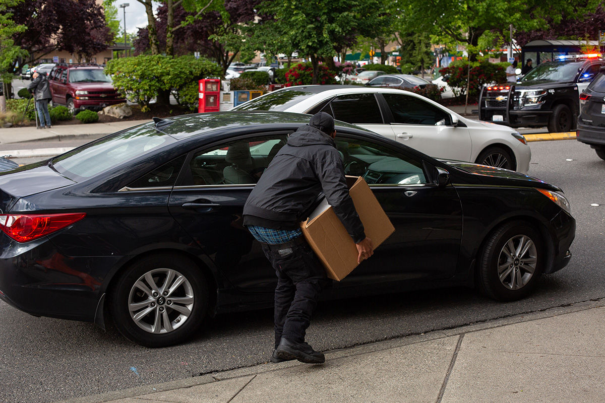 BELLEVUE, WA - MAY 31: A man carries a large box into a car outside of Bellevue Square Mall whlie looting takes place on May 31, 2020 in Bellevue, Washington. Protests due to the recent death of George Floyd took place in Bellevue in addition to Seattle, with looting in Bellevue and at least one burned automobile there. (Photo by David Ryder/Getty Images)