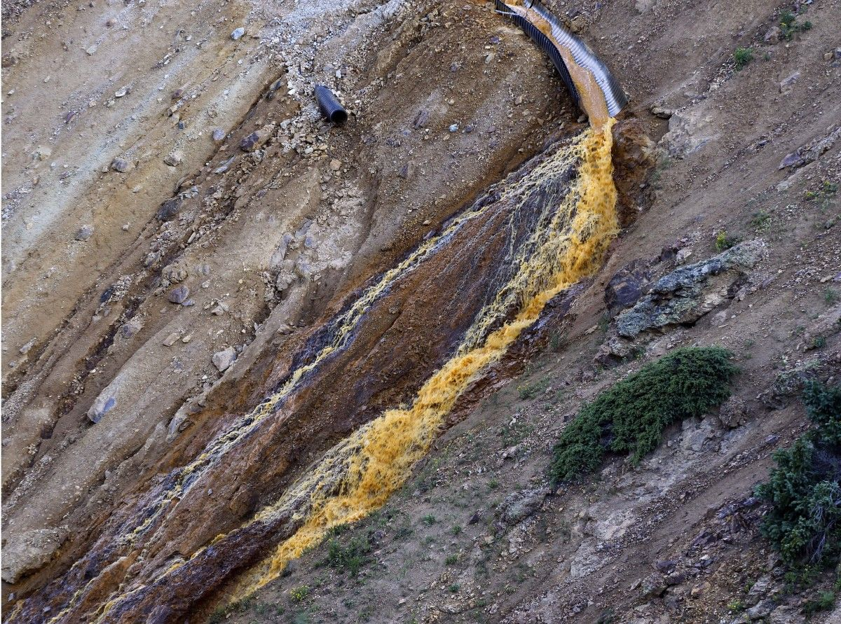 Wastewater flows from a trough and down a steep ravine at the site of the blowout at the Gold King mine which triggered a major spill of toxic wastewater, outside Silverton, Colo., Thursday, Aug. 13, 2015. It will take years, if not decades, and many millions of dollars to clean up and manage the toxic wastewater from a this Colorado mine that unleashed a 100-mile-long torrent of heavy metals, affecting the livelihoods of residents in three states, according to some experts. (AP Photo/Brennan Linsley)