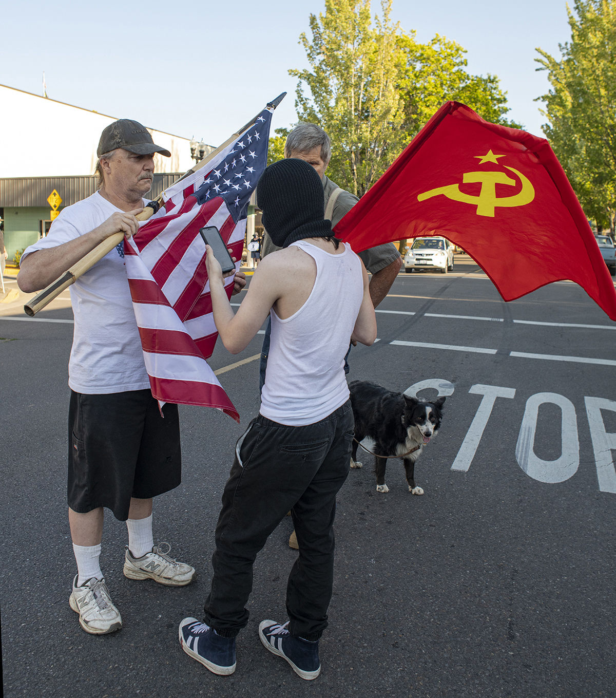 An attendee of the All Lives Matter rally, left with American flag, faces off with a counter protester., right, in black ski mask, with a flag with the communist hammer and sickle. About 250 people gathered at the Springfield, Oregon, library for what was billed as an All Lives Matter rally Friday at 7 p.m. About a dozen counter protesters also attended. The event was mostly peaceful, although a couple of minor scuffles broke out and one man was taken into custody by the Springfield police. By 9:30 p.m. both the protesters and the counter protesters dispersed. Photo by Dan Morrison