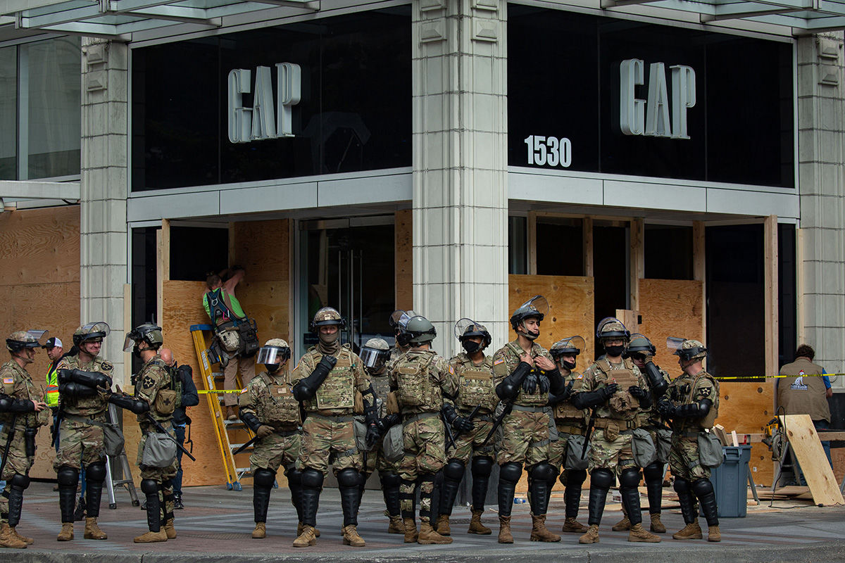 SEATTLE, WA - MAY 31: Washington National Guard personnel stand in front of a GAP store as nearby demonstrators gather to protest the recent death of George Floyd on May 31, 2020 in Seattle, Washington. Protests due to the recent death of George Floyd took place in Seattle and its suburb of Bellevue, with disturbances in Bellevue and at least one burnt automobile there.(Photo by David Ryder/Getty Images)