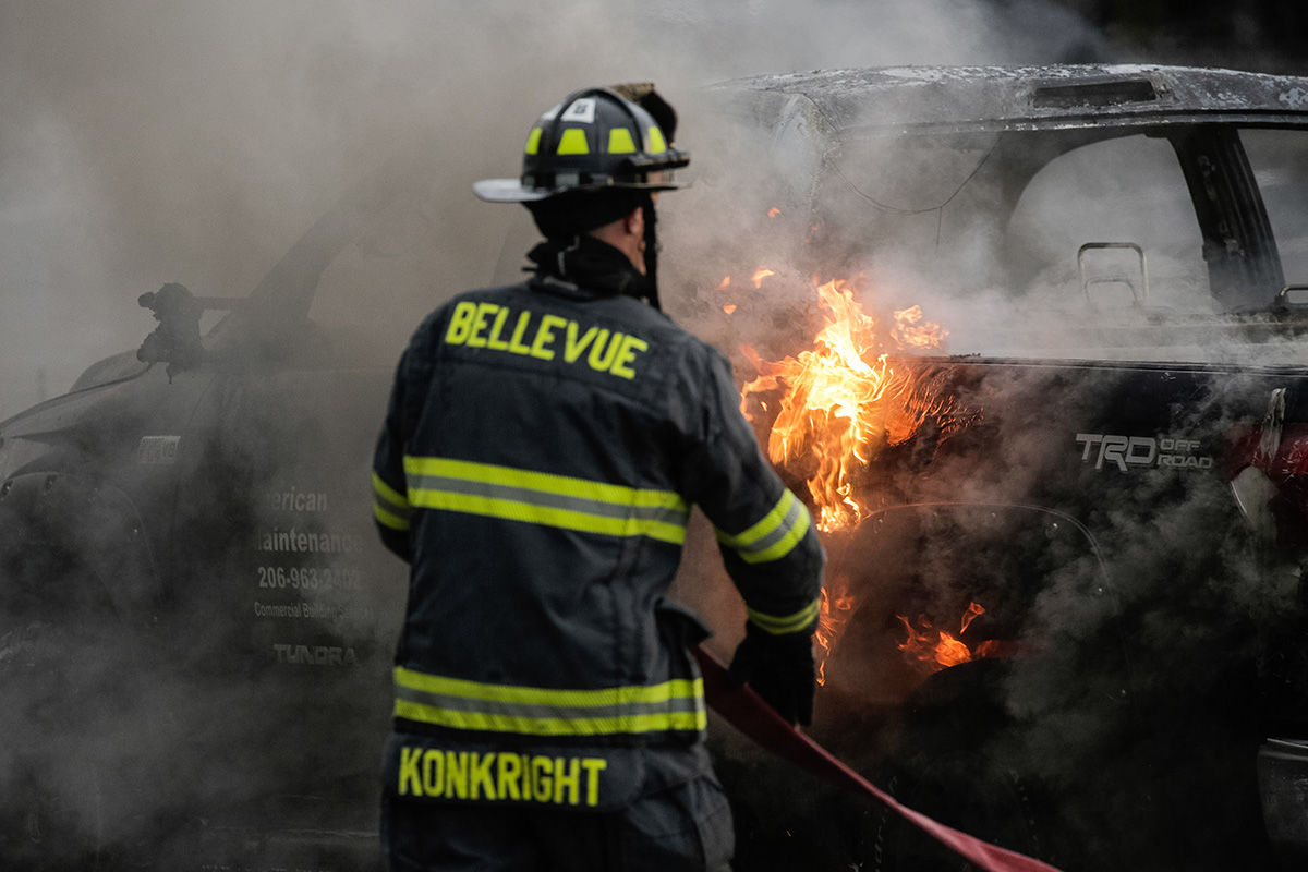 BELLEVUE, WA - MAY 31: A firefighter extinguishes a truck fire on May 31, 2020 in Bellevue, Washington. Protests due to the recent death of George Floyd took place in Bellevue in addition to Seattle, with looting in Bellevue and at least one burned automobile there. (Photo by David Ryder/Getty Images)